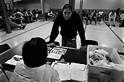 A man applies for food stamps at an outreach table set up on the main floor of the Millionair Club while others nap while waiting for work to come in. October 2006.