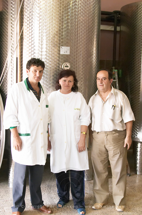 Enver Ulqini, oenologist and winemaker in front of a stainless steel fermentation tank together with two winery workers. Kantina Miqesia or Medaur winery, Koplik. Albania, Balkan, Europe.