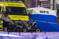 © Licensed to London News Pictures. 21/07/2021. London, UK. A quad bike sits in front of an ambulance and forensic tent at the scene following a fatal stabbing on Brixton Road, Brixton. Metropolitan Police Service (MPS) were called at 20:18BST to reports of an assault close to Brixton Underground Station. Despite efforts from police officers, paramedics from London Ambulance Service (LAS) and London's Air Ambulance the man was pronounced dead at the scene at the 20:45BST. Photo credit: Peter Manning/LNP