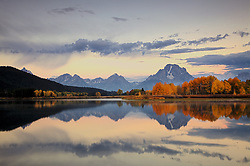 """Sunrise at Oxbow Bend at the peak of Autumn colors in Grand Teton National Park. The Oxbow Bend of the Snake River provides a great reflecting pool for the red and yellow aspens.<br /> <br /> For production prints or stock photos click the Purchase Print/License Photo Button in upper Right; for Fine Art """"Custom Prints"""" contact Daryl - 208-709-3250 or dh@greater-yellowstone.com"""