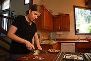 USA, Oregon, Eugene, young woman chopping garlic for dinner. MR