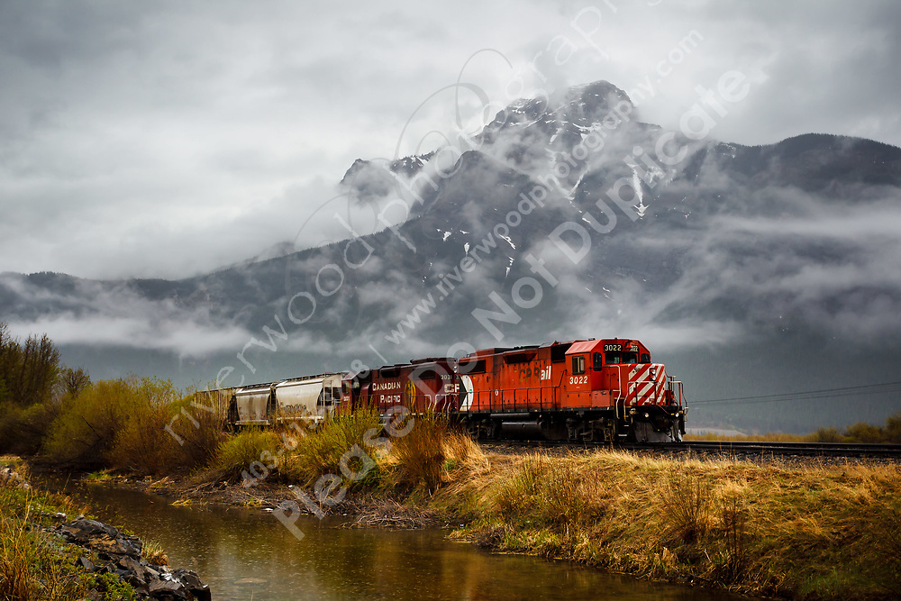 This CP Rail engine was sitting on the tracks just to the east of Exshaw. The cloud cover on the mountain behind provided a very cool contrast to the warmth of the dead grasses and water in the foreground...<br /> <br /> ©2013, Sean Phillips<br /> http://www.RiverwoodPhotography.com