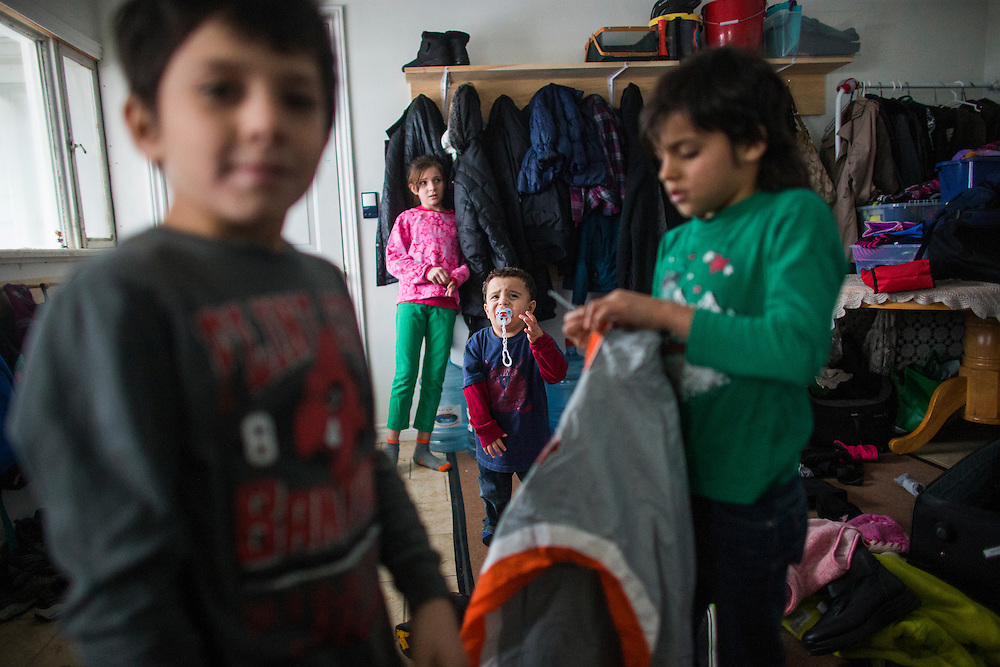 Syrian refugee Fadl Al Jasem (centre), cries as his brothers and sisters prepare to go outside, inside their temporary home in Picton, Ontario, Canada, Wednesday January 20, 2016.   (Mark Blinch for the BBC)