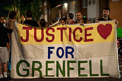© Licensed to London News Pictures. 16/06/2017. London, UK. A late night vigil is held for the victims of the Grenfell tower block in west London earlier this week. The blaze engulfed the 27-storey building killing 12 - with 34 people still in hospital, 18 of whom are in critical condition. The fire brigade say that they don't expect to find anyone else alive. Photo credit: Guilhem Baker/LNP