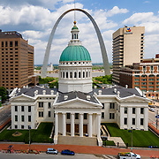 St. Louis Old Courthouse with Gateway Arch in background and Mississippi River. Grounds of Gateway National Park taken by drone aerial from outside the National Park space, above Kiener Plaza.