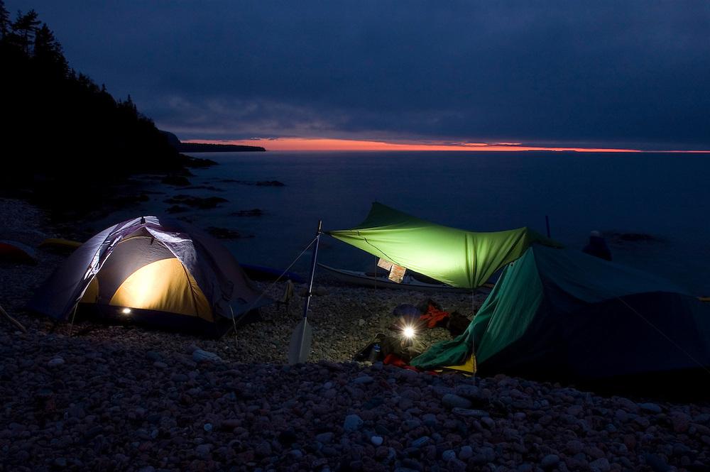 Sea kayaker's tents are illuminated at dusk in Lake Superior Provincial Park near Wawa Ontario Canada.