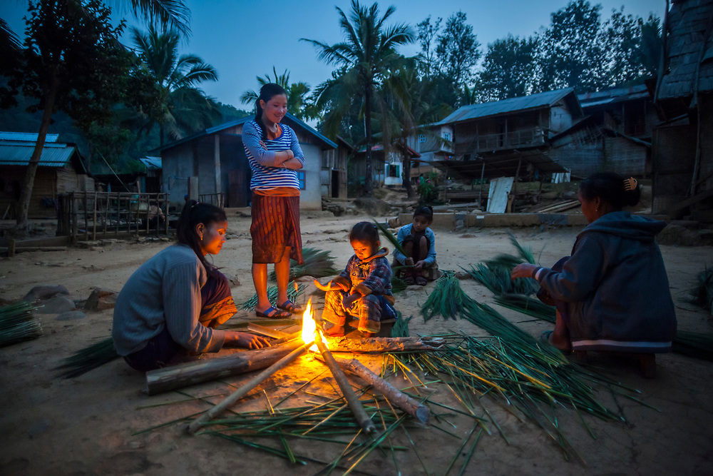 Women and children stay warm by a fire and process reeds used to manufacture brooms in Ban Had Dan, Laos. The clusters, wrapped with bamboo and made into brooms, are sold to neighboring Vietnam and fetch 3,000 kip ($0.37) - a cottage industry in this village. The village would only be partially inundated by proposed Dam #3 (whose construction has not yet commenced).
