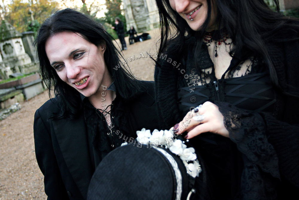 Darren Jack Powell, 34-year-old English man, is having fun with another member during a  cemetery tour organised by the Vampyre Connexion on Sunday, 2 December, 2006, in Nunhead Cemetery, South London, England. The Vampyre Connexion is the largest and most active of all the vampire groups in the United Kingdom, counting more than 100 members that for years have gathered regularly in London to share their common love for vampires and the Dark side of life. The Connexion raised from the hashes of the Vampyre Society, the first vampire appreciation group in 1995. The group believe in the fantasy of vampires and such creatures and live it to the full. Its  roots are to be found in the legends of Bram Stokerís Dracula. The group prints its own magazine, ëDark Nightsí featuring drawings, poetry, stories, photography and events. All of the members dress very peculiar clothing, and this is a very important part of the life of the group; it is respected with pride, taste and accuracy for the detail. Most like to dress to be elegant in a range of styles from regency to Victorian, some sew their own. In addition members visit art galleries, cemeteries, churches and cathedrals, attend gigs and concerts, and hold their own parties throughout the year, Halloween being the biggest and scariest one. Membership is open to all, the only qualification: being a love of all things Vampyric.**ItalyOut**