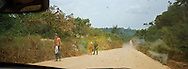 Villagers walking along the road as traffic passes along Highway BR163. The highway ran from Santarem on the banks of the Tapajos river for one thousand miles south into the state of Mato Grosso and was unpaved except for a small stretch at its northern end. The area surrounding the highway was the front line in the battle between local communities and environmentalists who tried to prevent to spread of rainforest destruction by illegal loggers and companies which bought and seized land for use in cattle ranching and growing soy beans for export from Brazil via the port at Santarem.