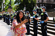 A young woman protester walks filming herself at a protest against the state government's lockdown in front of a police line.The groups who have organised the many Freedom Day protest over the last 3 months, attempted to march to State Parliament on Melbourne Cup Day demanding the sacking of Premier Daniel Andrews for the lockdown and attacks on their civil liberties, where they were met with a heavy police presence.  (Photo by Michael Currie/Speed Media)