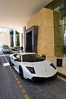 Luxury vehicles including Lamborghini sports cars outside the Raffles Dubai Hotel, Dubai, United Arab Emirates