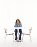Out of focus woman in casual clothes sitting with arms on table and thinking. Table on white set with empty chairs