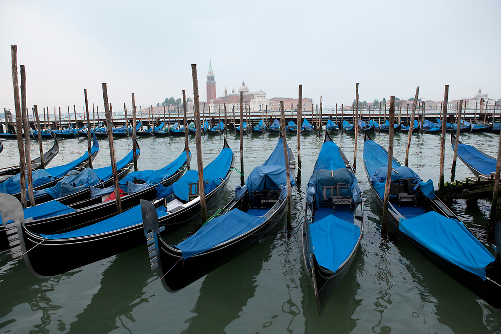 Gondolas docked in a row with blue covers and the church of San Giorgio Maggiore across the lagoon