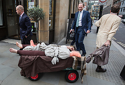 © Licensed to London News Pictures. 04/09/2015. London, UK. City workers look amused at the passing 'dead cart'. Actors in traditional costumes took part in a procession from Minories (near the Tower of London) to St Botolph without Aldgate Church in which they dragged a cart with 'plague victims' and yelled 'bring out your dead' to passing members of public. This is to mark 350 years since the plague pit at church was completed. It also marks the opening of the Great Plague Festival which runs until September 6th. Photo credit : James Gourley/LNP