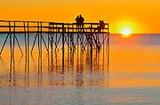 People enjoying a sunrise on a 'stick' pier over Lake Winnipeg<br /> Matlock<br /> Manitoba<br /> Canada