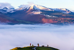 © Licensed to London News Pictures. 07/12/2020. Keswick UK. People stand at the top of Latrigg fell & watch the fog this morning that is covering the town of Keswick bellow as much of the UK has been affected by freezing fog today. Photo credit: Andrew McCaren/LNP
