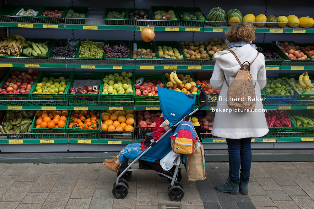 A mother and child stop to choose nutritious fruit and veg from the shelves of oranges, bananas, apples and grapes, outside a shop in Bromley town centre where local businesses offer fresher and cheaper foodstuffs than the larger supermarkets, on 3rd February 2020, in London, England.