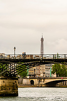 People crossing the Pont des Arts (pedestrian bridge) across the River Seine with the Eiffel Tower in background, Paris, France.