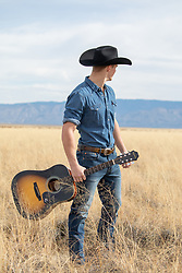 cowboy with a guitar on a ranch