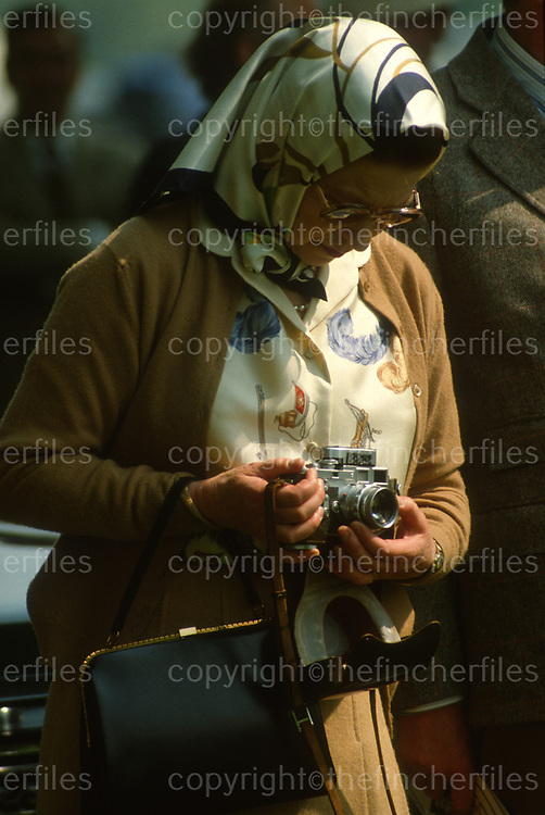 Her Majesty Queen Elizabeth seen off duty at the Royal Windsor Horse Show in Windsor, UK in May 1982. She has her Leica camera around her neck. Photographed by Jayne Fincher