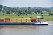 Nederland, Varik, 9-6-2018Een binnenvaartschip vaart over de Waal beladen met containers richting Duitsland .In dit deel van de Waal zijn de kribben verlaagd of vervangen door langsliggende dammen om de waterafvoer te verbeteren .Foto: Flip Franssen