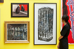 "© Licensed to London News Pictures. 05/06/2018. LONDON, UK. A staff member views (C) ""Five Grand"" by Luke Wade at a preview of the 250th Summer Exhibition at the Royal Academy of Arts in Piccadilly, which has been co-ordinated by Grayson Perry RA this year.  Running concurrently, is The Great Spectacle, featuring highlights from the past 250 years.  Both shows run 12 June to 19 August 2018.  Photo credit: Stephen Chung/LNP"