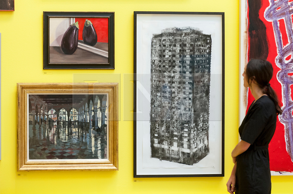 """© Licensed to London News Pictures. 05/06/2018. LONDON, UK. A staff member views (C) """"Five Grand"""" by Luke Wade at a preview of the 250th Summer Exhibition at the Royal Academy of Arts in Piccadilly, which has been co-ordinated by Grayson Perry RA this year.  Running concurrently, is The Great Spectacle, featuring highlights from the past 250 years.  Both shows run 12 June to 19 August 2018.  Photo credit: Stephen Chung/LNP"""
