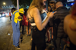 © Licensed to London News Pictures . 01/11/2015 . Manchester , UK . A man dressed as a Minion clings to a lamppost as others queue for taxis , at Deansgate Locks . Halloween revellers , wearing make up and costumes , out and about in Manchester City Centre . Photo credit : Joel Goodman/LNP