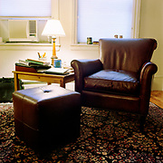 A dark purplish looking leather lounge chair and matching square footrest on a patterned Oriental style carpet, on a wooden floor.There is a simple wood side table to the left of the chair, piled with booklets and notebooks, an wooden lamp, and a white jar of pens and other things, as well as a phone and a cup. There is a black briefcase in the background, against the rear wall and below an air conditioner, and two windows covered with blinds.