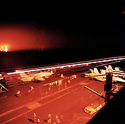 The glow and trails of night manoeuvres seen from an upper deck of the US Navy's Harry S Truman aircraft carrier whilst on exercise somewhere in the Persian Gulf. <br />