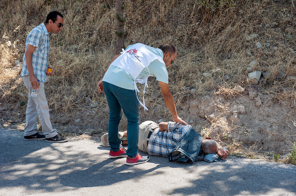 MSF translators Bashir and Rashid try to wake up a  Syrian refugee who was sleeping by the road. The man later told us that he was so tired from walking that he couldn't look for a better shelter. Refugees land at the northern shores of the island of Lesbos and then they have to walk the 9 hour distance to one of the camps.