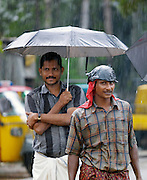 Men sheltering from the rain during the monsoon, Cochin, Kerala, India
