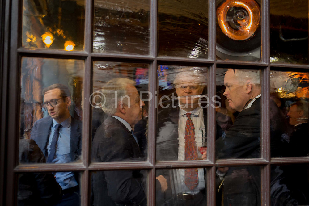 Seen through the distorting glass of a City pub on Lime Street, male businessman enjoy after-work drinks, on 10th May 2017, in the City of London, England.