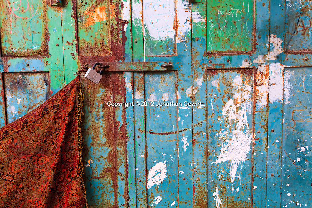 Closeup view of a colorful, rusty, locked metal door on a shop front in the Old City of Jerusalem. WATERMARKS WILL NOT APPEAR ON PRINTS OR LICENSED IMAGES.