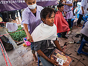 22 OCTOBER 2016 - BANGKOK, THAILAND: Students from a barber college give free haircuts to mourners at Sanam Luang in Bangkok. Sanam Luang, the Royal Ceremonial Ground, was packed Saturday with more than 100,000 people mourning the Monarch's death. The King died Oct. 13, 2016. He was 88. His death came after a period of failing health. Bhumibol Adulyadej was born in Cambridge, MA, on 5 December 1927. He was the ninth monarch of Thailand from the Chakri Dynasty and is also known as Rama IX. He became King on June 9, 1946 and served as King of Thailand for 70 years, 126 days. He was, at the time of his death, the world's longest-serving head of state and the longest-reigning monarch in Thai history.       PHOTO BY JACK KURTZ