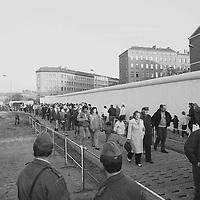"""Die beiden Grenzsoldaten der DDR haben eine für sie völlig neue Rolle eingenommen.Sie blicken gebannt auf ihre Landsleute, die sich in einer endlosen Reihe für den ersten Westspaziergang fein gemacht haben. Im Hintergrund das Gebäude mit der markanten Ecke war der Sitz vom """"Klub der Volkssolidarität"""", in dem sich sicherlich so manche feuchtfröhliche Runde zusammenfand."""