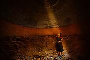 Jenna, aged 15, standing inside a large brick-firing kiln, O Sra Lav, Battambang, Cambodia