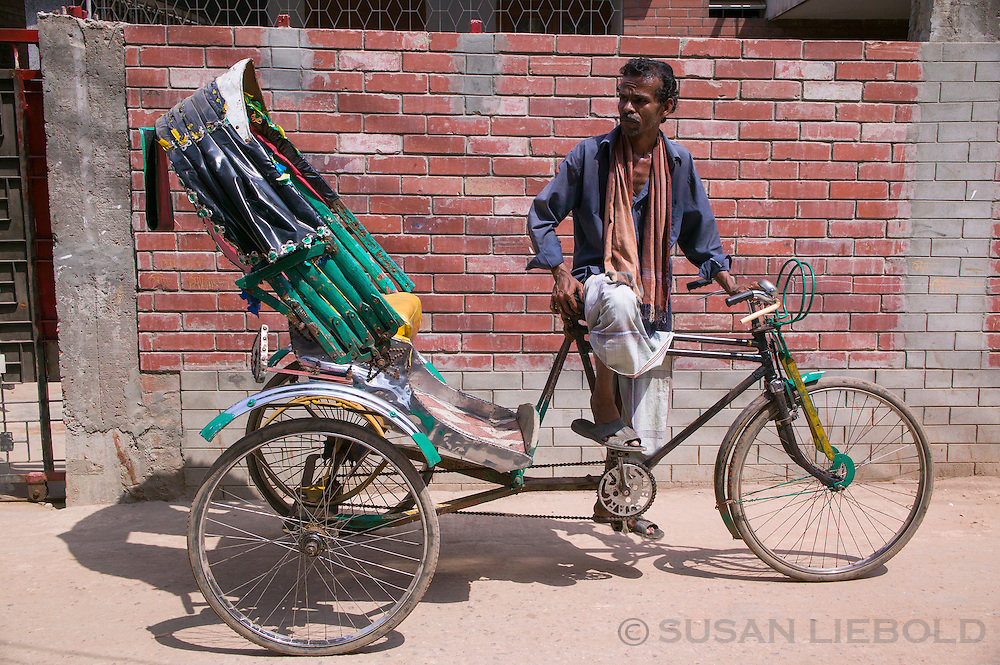 Jalal standing with his rickshaw waiting for a customer.