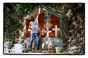 SHOT 1/30/16 2:09:16 PM - Porfidio Guerrero of Sayulita, Mexico constructs a roadside capilla along Highway 200 just outside of Sayulita, Mexico. The capilla was erected on the site of a traffic accident that killed four young girls in 2015. Guerrero was friends with the girls families and built the capilla with crosses at the site. The capillas are common along the roads and highways of Mexico which is heavily Catholic and are often dedicated to certain patron saints or to the memory of a loved one that has passed away. Often times they contain prayer candles, pictures, personal artifacts or notes. (Photo by Marc Piscotty / © 2016)
