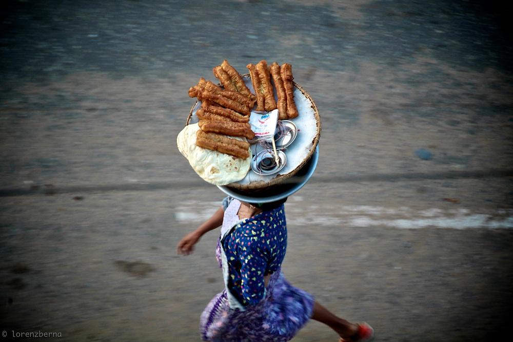 A street food seller in Myanmar is walking the street of Bago with breakfast food balanced on the head. Photo by Lorenz Berna