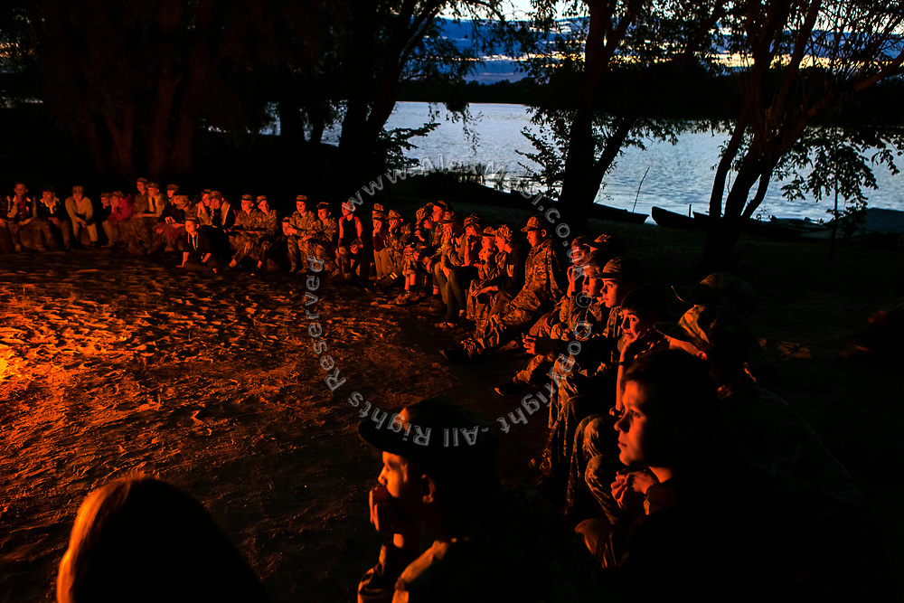 Youngsters participating to the ultra-nationalistic Azovets children's camp are sitting together around the evening fire, on the banks of the Dnieper river in Kiev, Ukraine's capital.