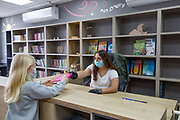Schooling under COVID-19 Pupil and librarian with protective mask in deserted library at a Primary school. The outbreak of COVID-19 has forced governments around the world to impose a civil quarantine. The outcome of this is limited contact between people including students and teachers and minimal social interaction. Photographed at Kedem Primary School, Israel