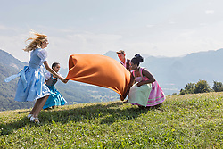 Teenage friends spreading picnic blanket on grass landscape, Bavaria, Germany