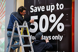 © Licensed to London News Pictures. 28/11/2014. LONDON, UK. A Black Friday weekend deal poster is being put up on a shop window whilst people shopping on Oxford Street to take advantage of Black Friday discounts on Friday, 28 November 2014. Photo credit : Tolga Akmen/LNP