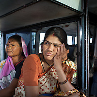 """Vandana Dube (foreground), the manager of Dharkan 107.8 travels on a local bus with her program-maker colleague Ramvati Adivasi. Before the official launch of the community radio station in July 2009, Dube and her colleagues have recorded several programs informing women of government health services. They then travel to villages to play these programs to a local audience. Dube calls the airing of these pilot shows """"narrowcast"""" in anticipation of the imminent """"broadcast"""". As well as her role at Dharkan 107.8, Adivasi is is an ASHA (local female health advisor). She provides a free referral service to local women, keeping them in touch with government health services. Adivasi receives a fee from the government for every referral. This is one means by which the government and partners UNICEF are increasing the rate of institutional deliveries in Madhya Pradesh. ..Shivpuri district in Madhya Pradesh suffers from poor health outcomes. Of particular concern is the high rate of maternal mortality. One of the Indian government's aims, with partners Unicef, is to encourage the population to adopt practices to improve sanitation and health practices. In an area made up of traditionally disadvantage groups and suffering low literacy rates, this can be a challenge. ..A survey found that radio was the most readily accessible media by the Shivpuri community with more than half saying they tuned in several times a day. ..Dharkan 107.8 FM will go on air in July. The station that will broadcast to 75 villages in a 15-kilometer radius reaching 170,000 people...Rather than preaching educational messages, the station, which is already producing pilot programs, uses humor and folk artists performing in the local language to entertain and inform their audiences. There is a major impact, especially on women, who are contributing their voices to such wide-ranging issues as caste discrimination, female feticide and women's empowerment. ..Photo: Tom Pietrasik.Shivpuri, Madhya Pradeh. India."""