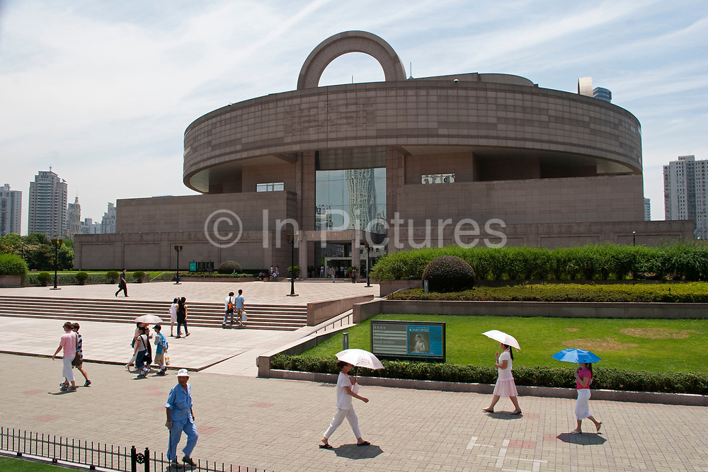 Shanghai Museum in Peoples Square, downtown Shanghai. People shielding themselves from the sun with umbrellas walk past this popular museum on a sunny summer day.