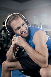 Mid adult man taking rest after workout in the gym and listening to music, Bavaria, Germany
