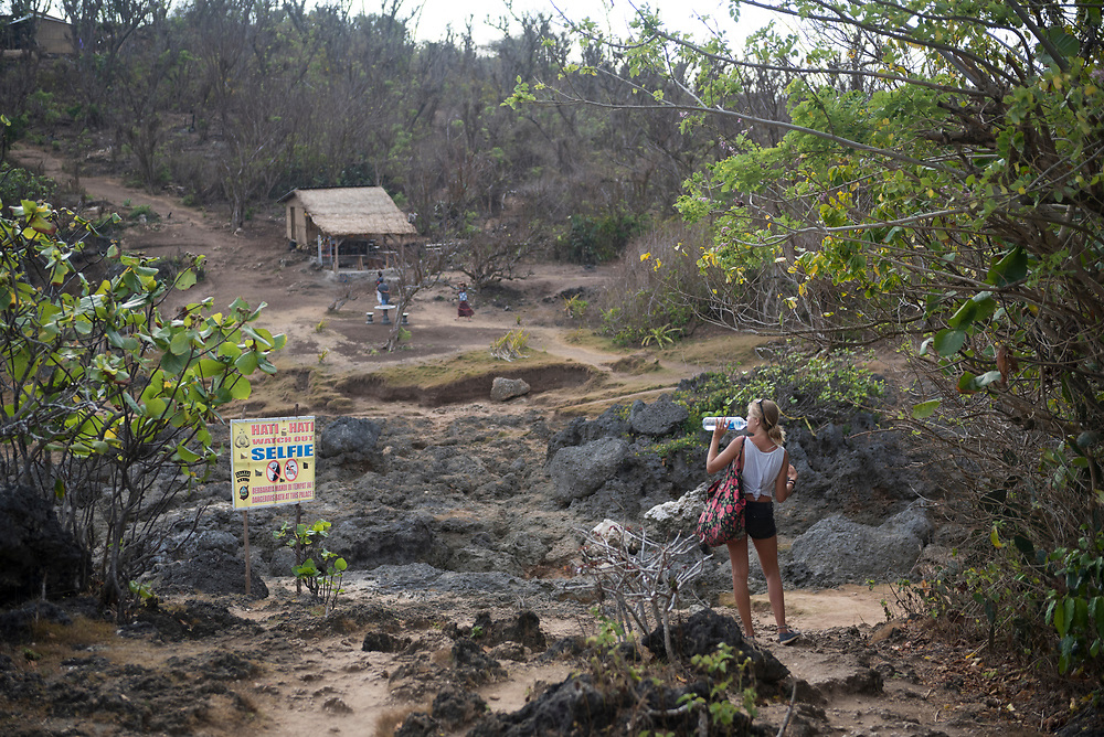 Nusa Penida, Indonesia - October 3, 2017: Denise, from Spain, takes a drink of water near a sign warning of the dangers of taking a selfie near the steep drop-offs at Angel's Billabong, Nusa Penida, Bali.