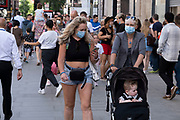 Now that most restrictions have come to an end, Oxford Street shopping district is busier than much of the last 18 months as shoppers return in their droves and retail business looks set to bounce back on 10th August 2021 in London, United Kingdom. Many people are wearing face masks in crowded places like this but they are no longer mandatory, while government advice suggests that it is advised to wear a face covering in busy public places inside and on transport, many people are still wearing them outside.