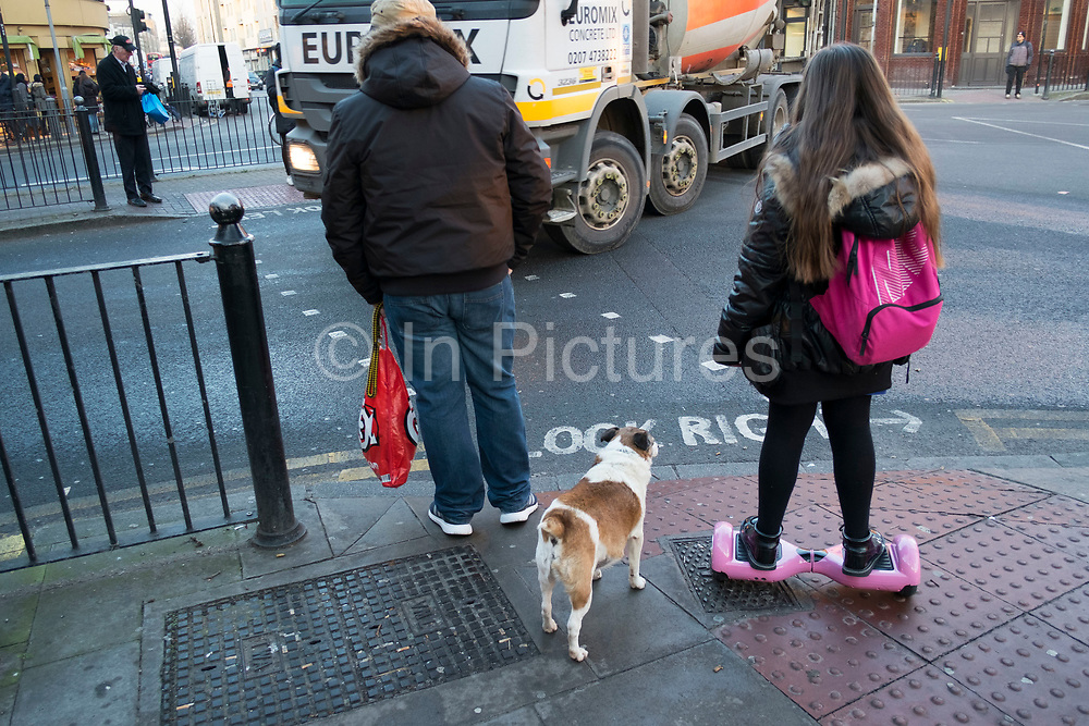 Young girl going home from school on her hoverboard, accompanied by a guardian and her dog. Hackney, London, England, UK. A self-balancing two-wheeled board, or self-balancing electric scooter, also commonly referred to as a hoverboard, is a type of portable, rechargeable battery-powered scooter. They typically consist of two wheels arranged side-by-side, with two small platforms between the wheels, on which the rider stands. The device is controlled by the rider's feet, standing on the built-in gyroscopic, sensored pads.